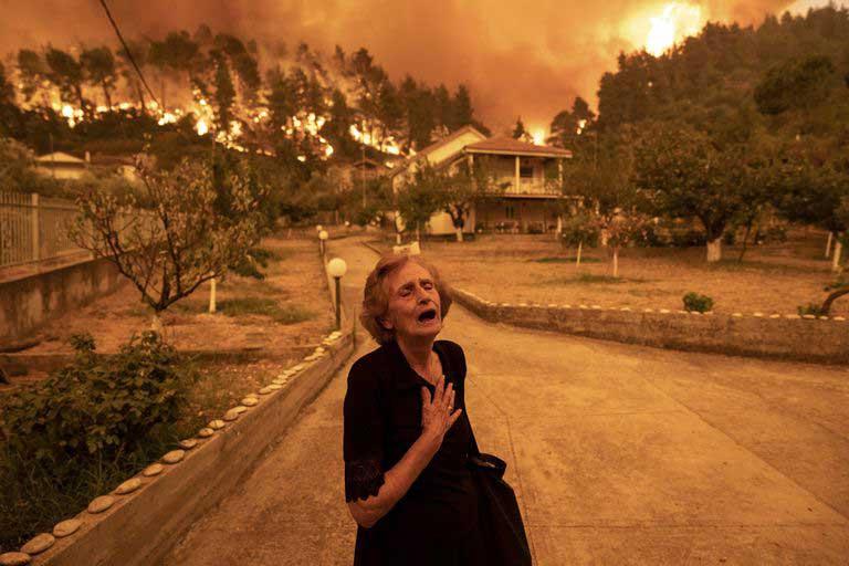 mujer desolada y superada por el fuego en Grecia